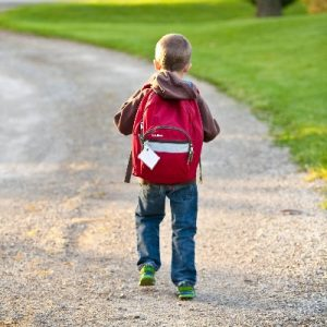 Kind mit rotem Schulrucksack